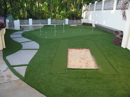 backyard synthetic turf putting green with sand trap and chipping mat
