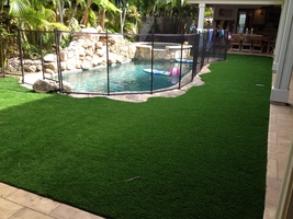 back yard pool with surrounding artificial turf